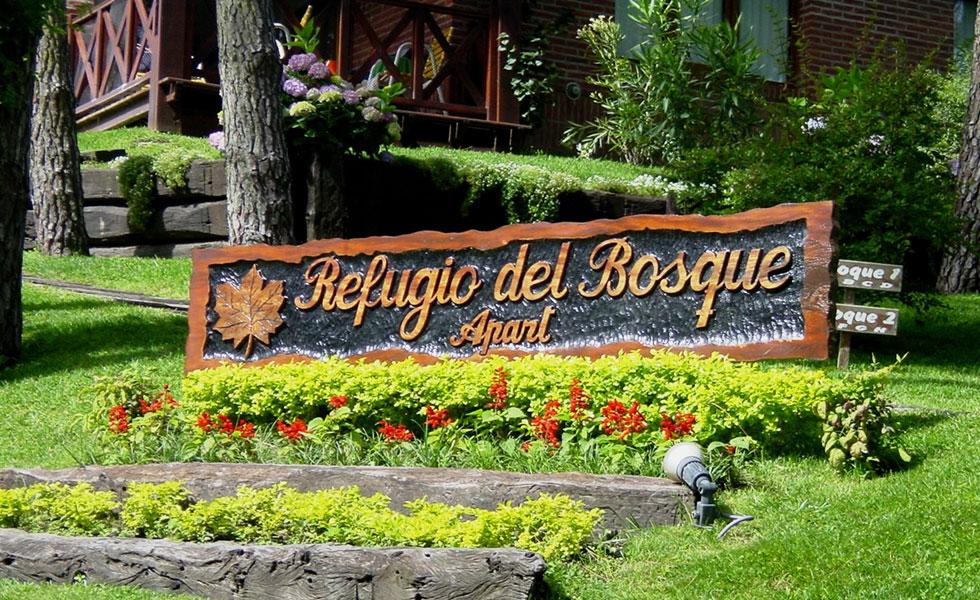 Frente flores y cartel de Refugio del bosque